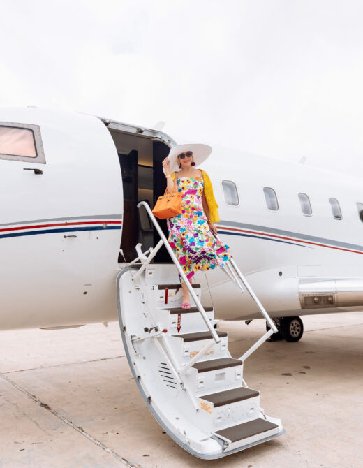 Sheree Frede of the SheShe Show standing on stairs leading into private jet wearing a floral dress and big white hat!