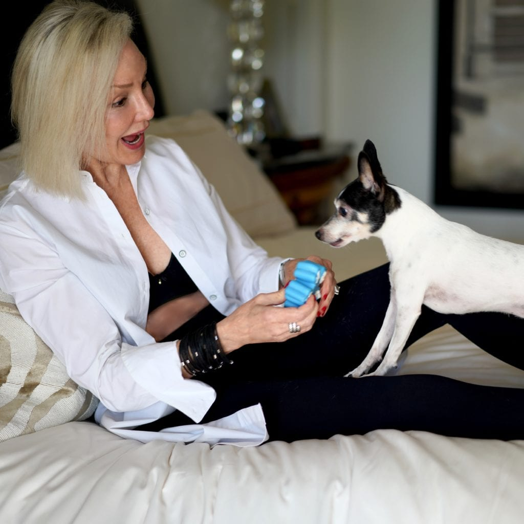 Long white shirt over black bra by Soma Intimates & black leggings playing with Toy Fox Terrier dog on the bed