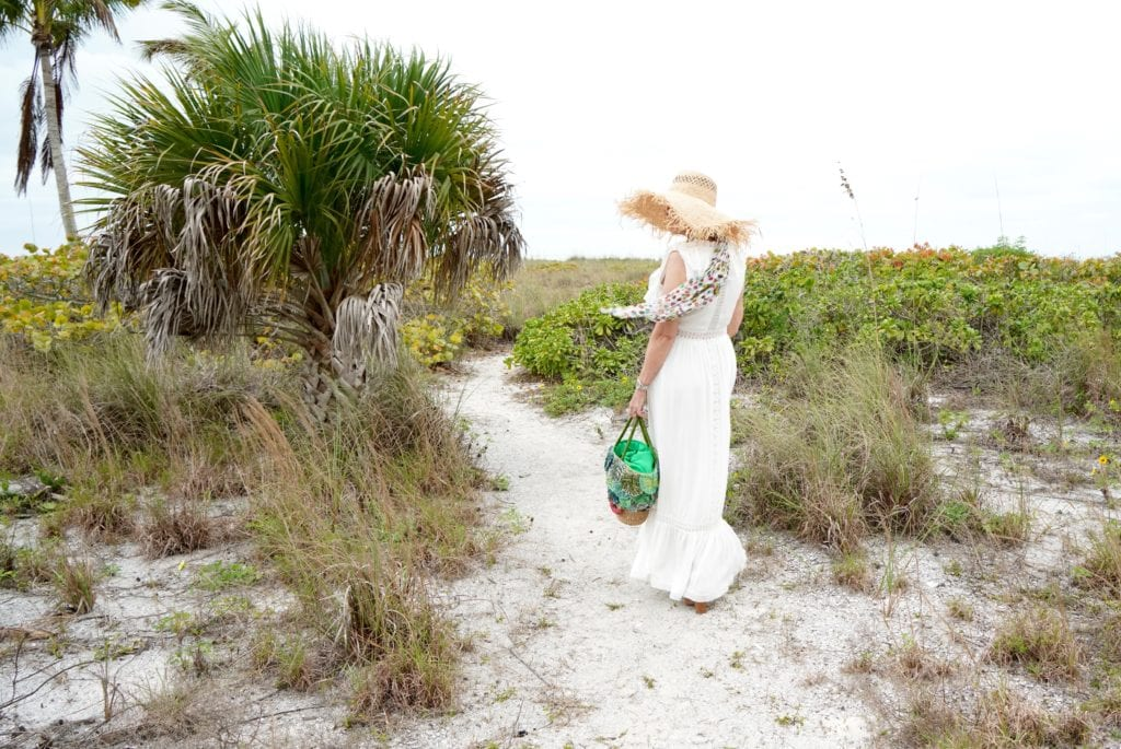 white maxi dress with ruffle details- large green straw tote bag-large straw hat-tropical sand dunes