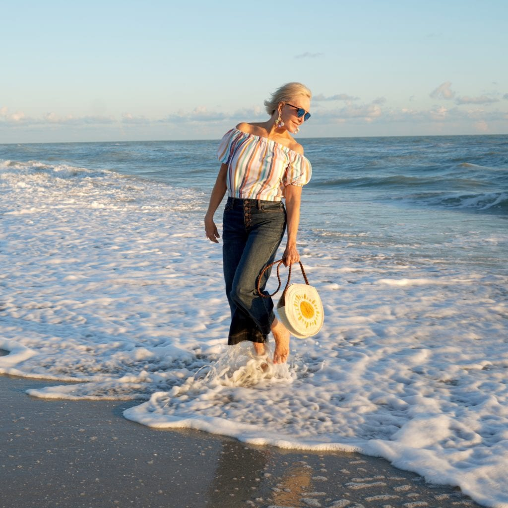 stripe off the shoulder top, cropped denim jeans with button fly, straw circle bag, barefoot walking along the beach
