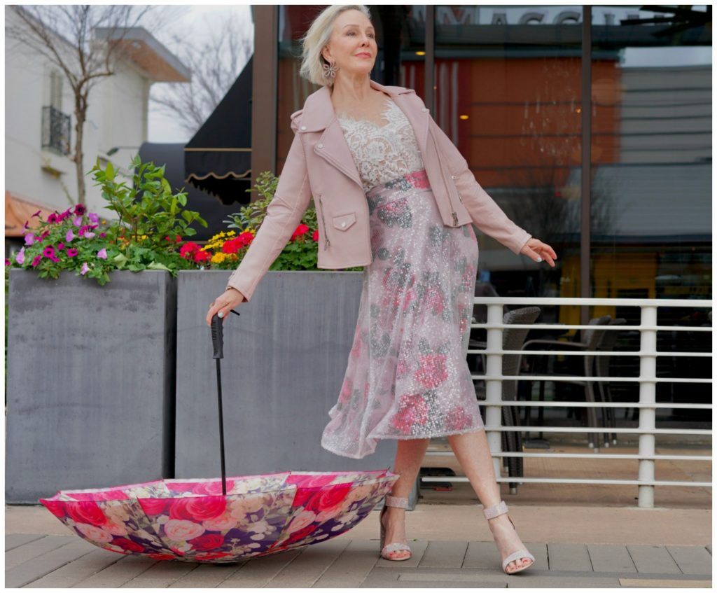 Sheree Frede standing in front of pretty spring flowers wearing a pink floral skirt and blush leather jacket and pink floral umbrella