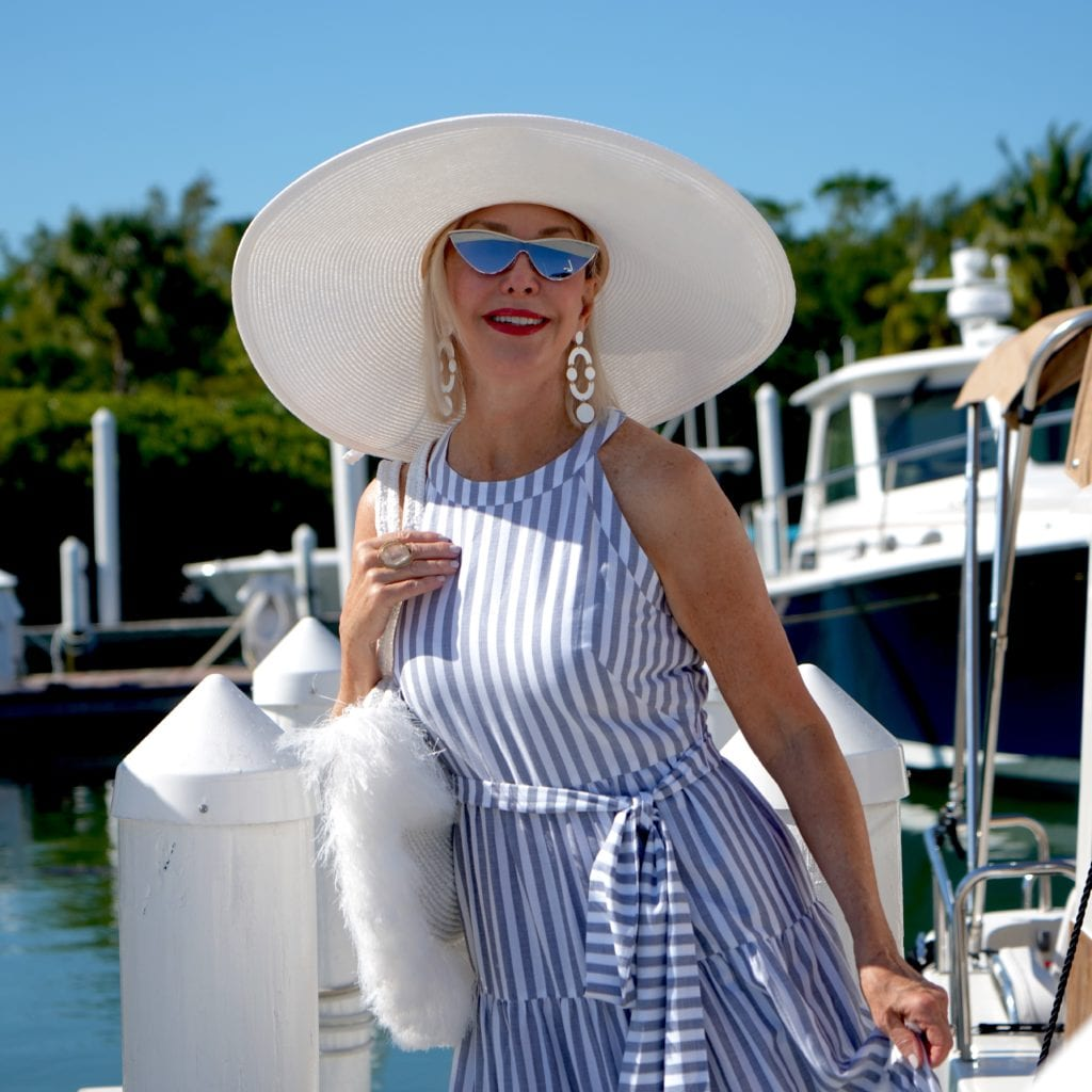 white wide brimmed hat and blue and white stripe dress