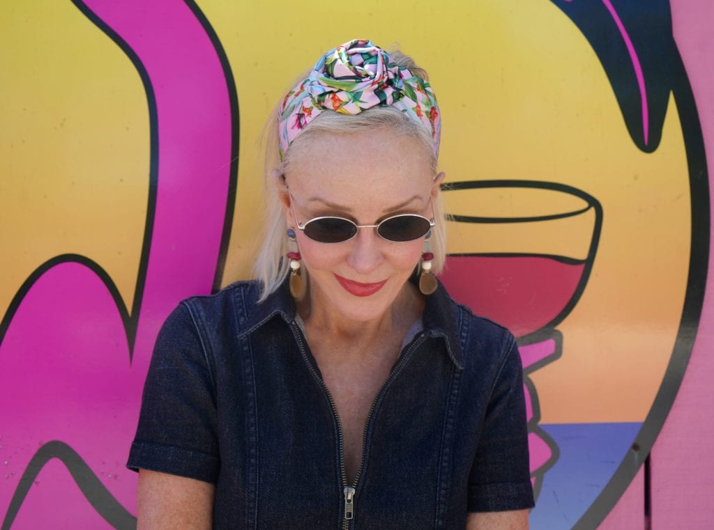 Sheree Frede of the SheShe Show wearing a floral headband and oval wire rimmed sunglasses