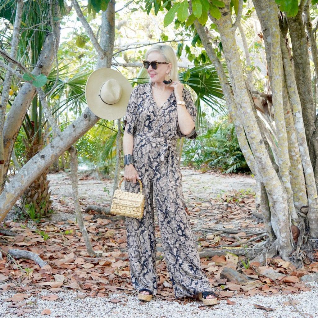 snakeskin print jumpsuit, bamboo bag, black wedge sandals, sunglasses, tropical setting