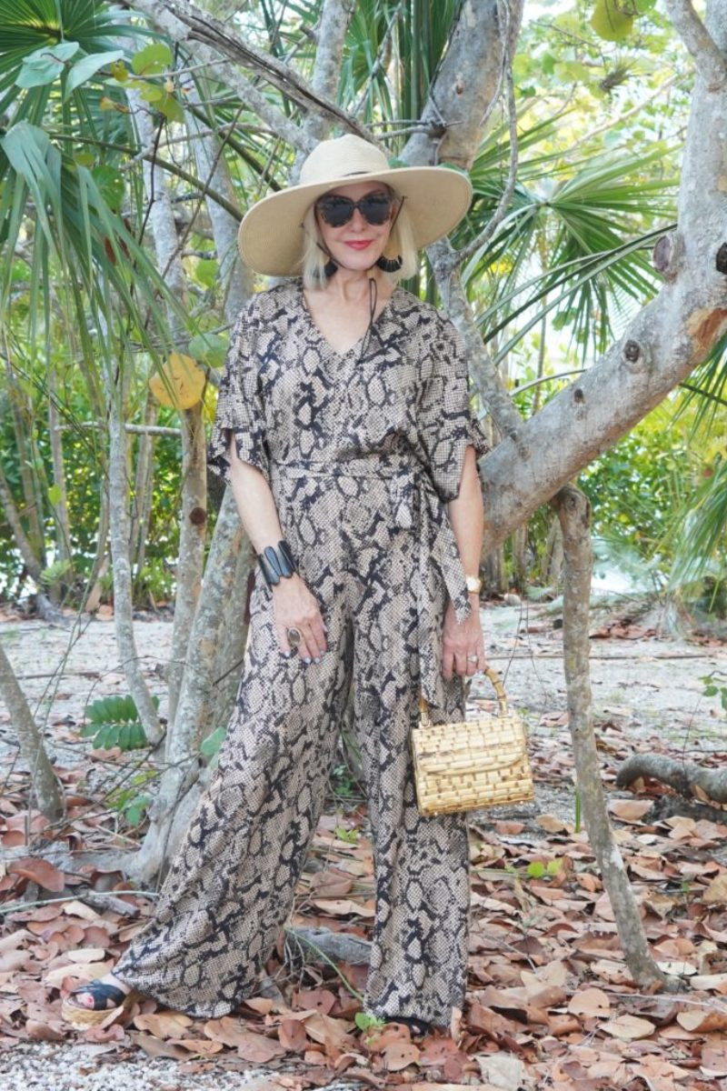 snakeskin print jumpsuit, bamboo bag, black wedge sandals, sunglasses, tropical setting