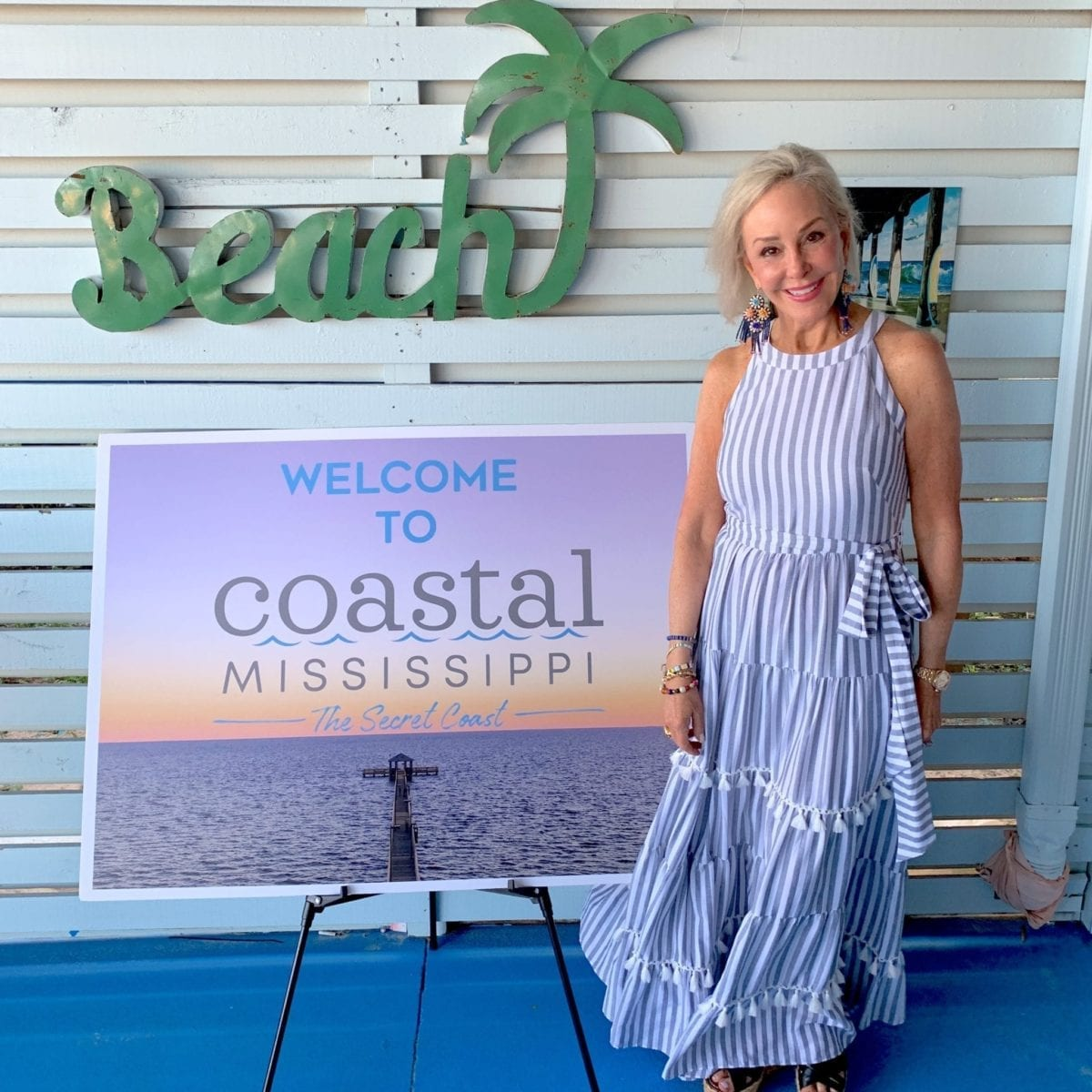 Sheree Frede of the SheShe Show wearing a blue dress by Coastal Mississippe sign