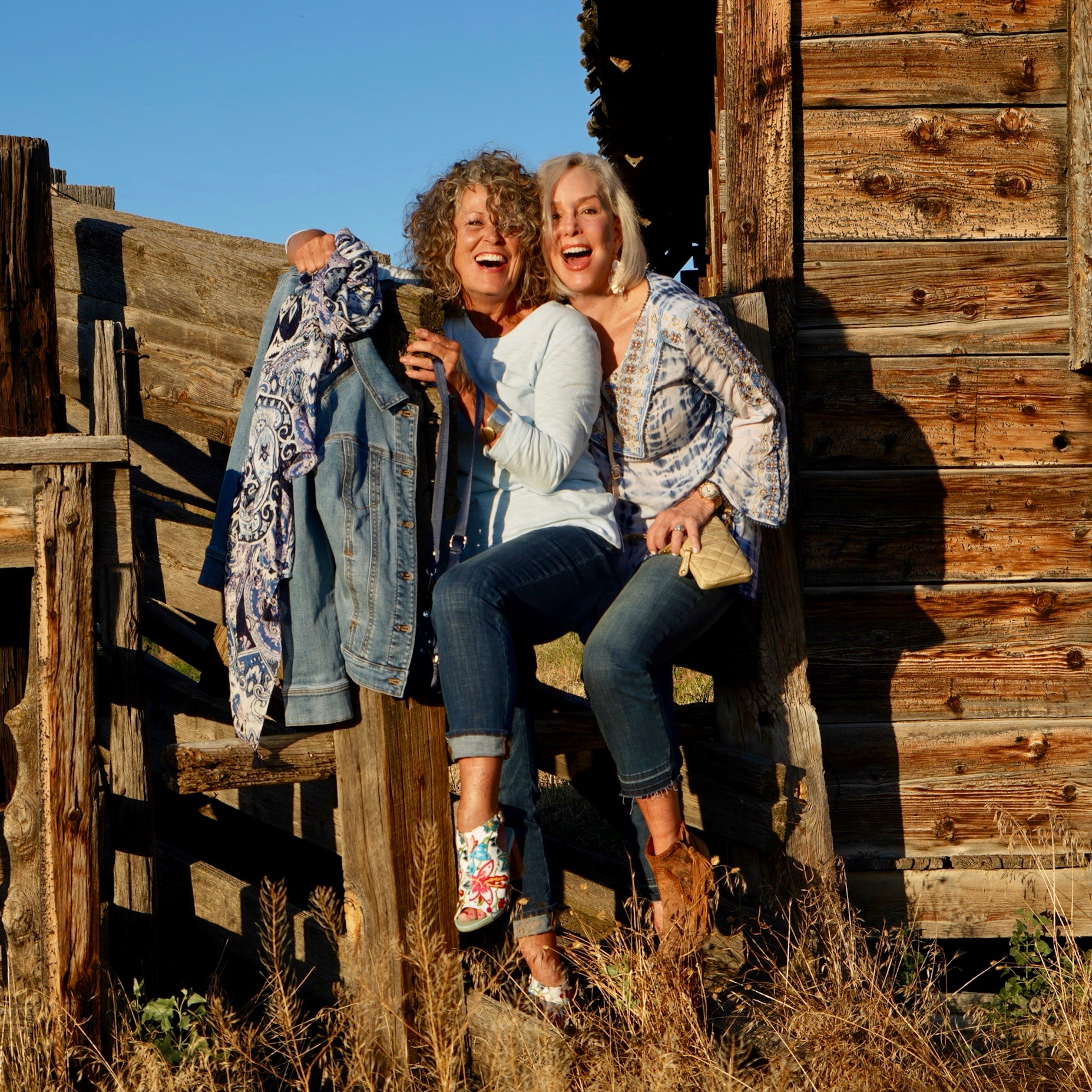 Ruthie and Sheree wearing jeans by a wood fence