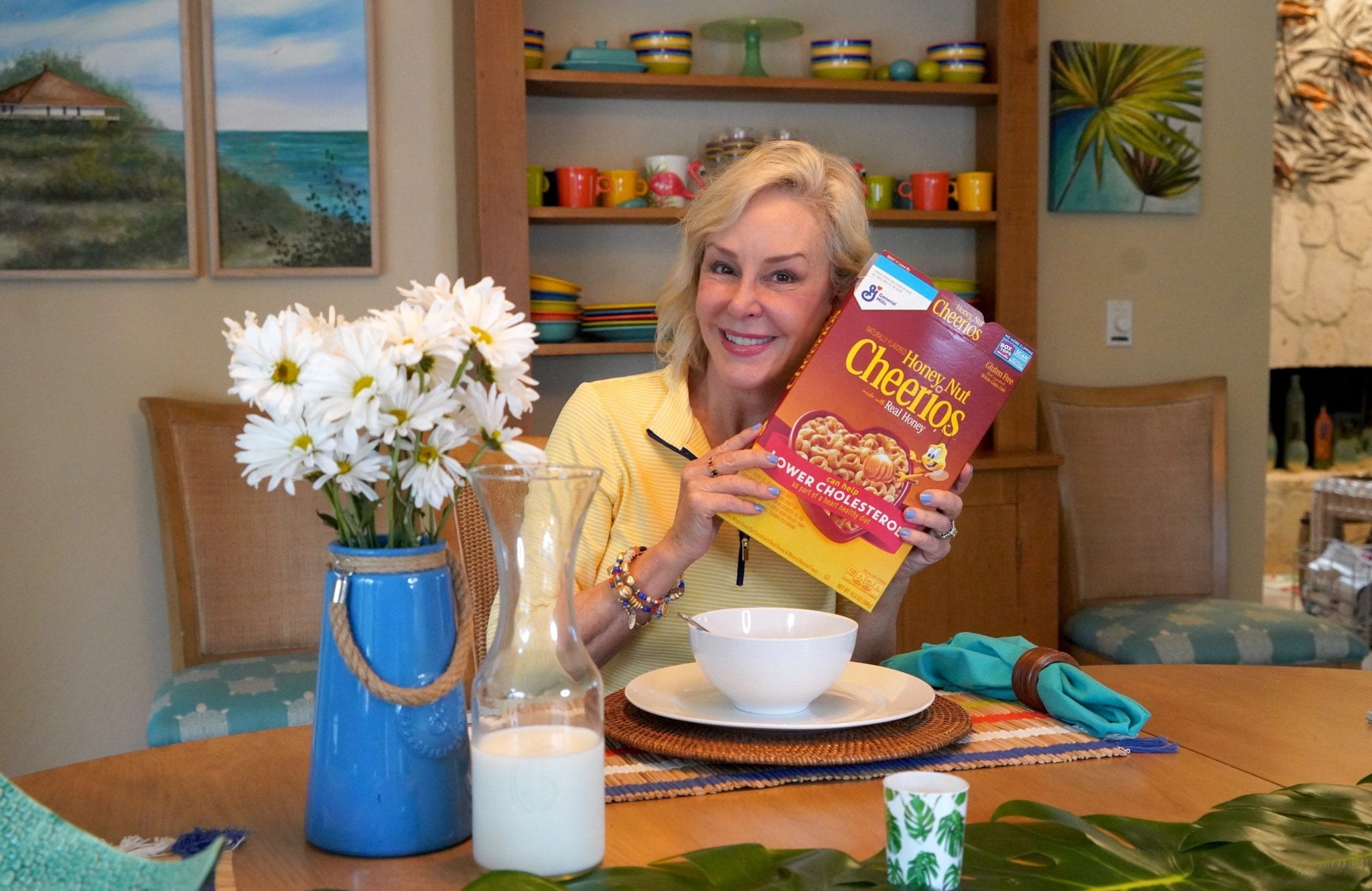 SheSheShow at breakfast table pointing at Cheerio's box