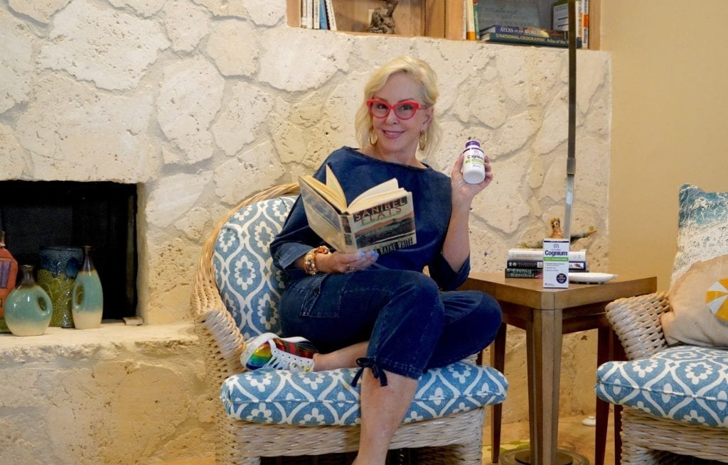 Sheree of the SheShe Show reading a book sitting in chair
