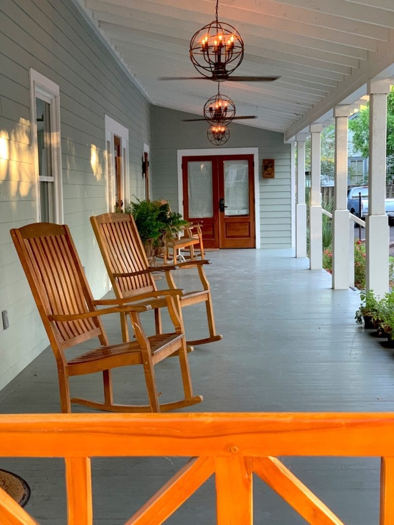 rocking chairs on big front porch with orange wood railing