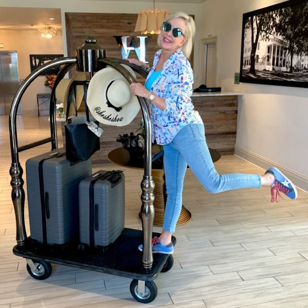 Sheree of the SheShe Show on luggage cart with suitcases