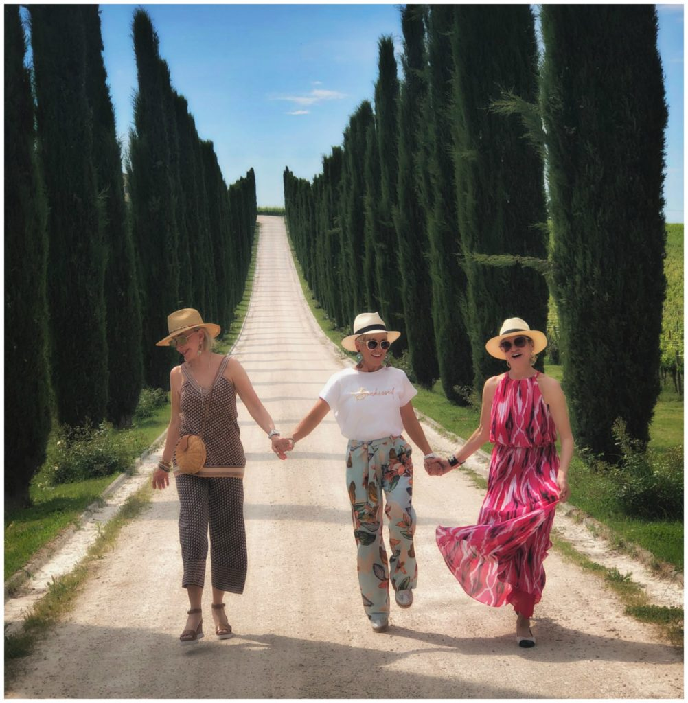 Sheree, Shauna, and Jamie holding hands walking down a road lined with Italian Cypress