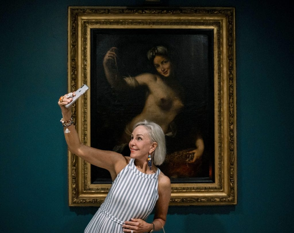 Sheree of SheShe Show posing in front of antique portrait