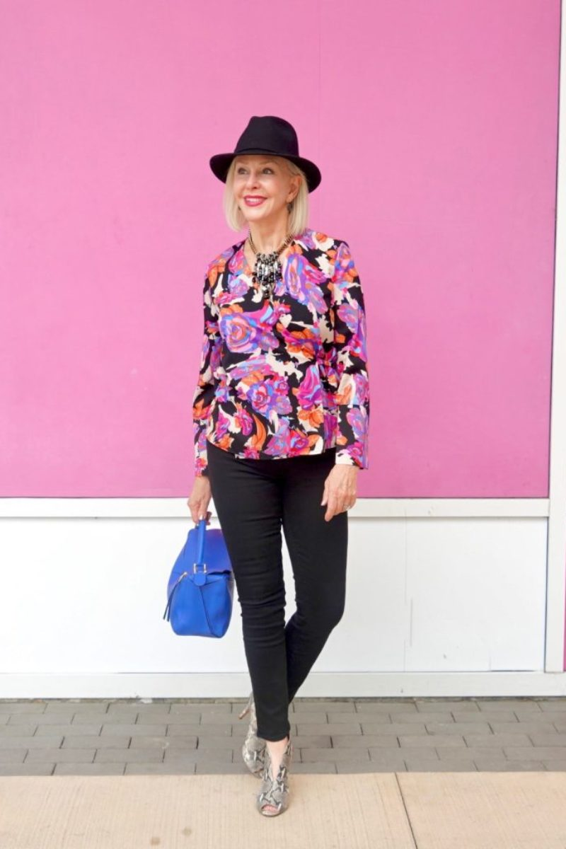 Sheree Frede of the SheShe Show wearing bright colored top, black jeans wearing black fedora hat