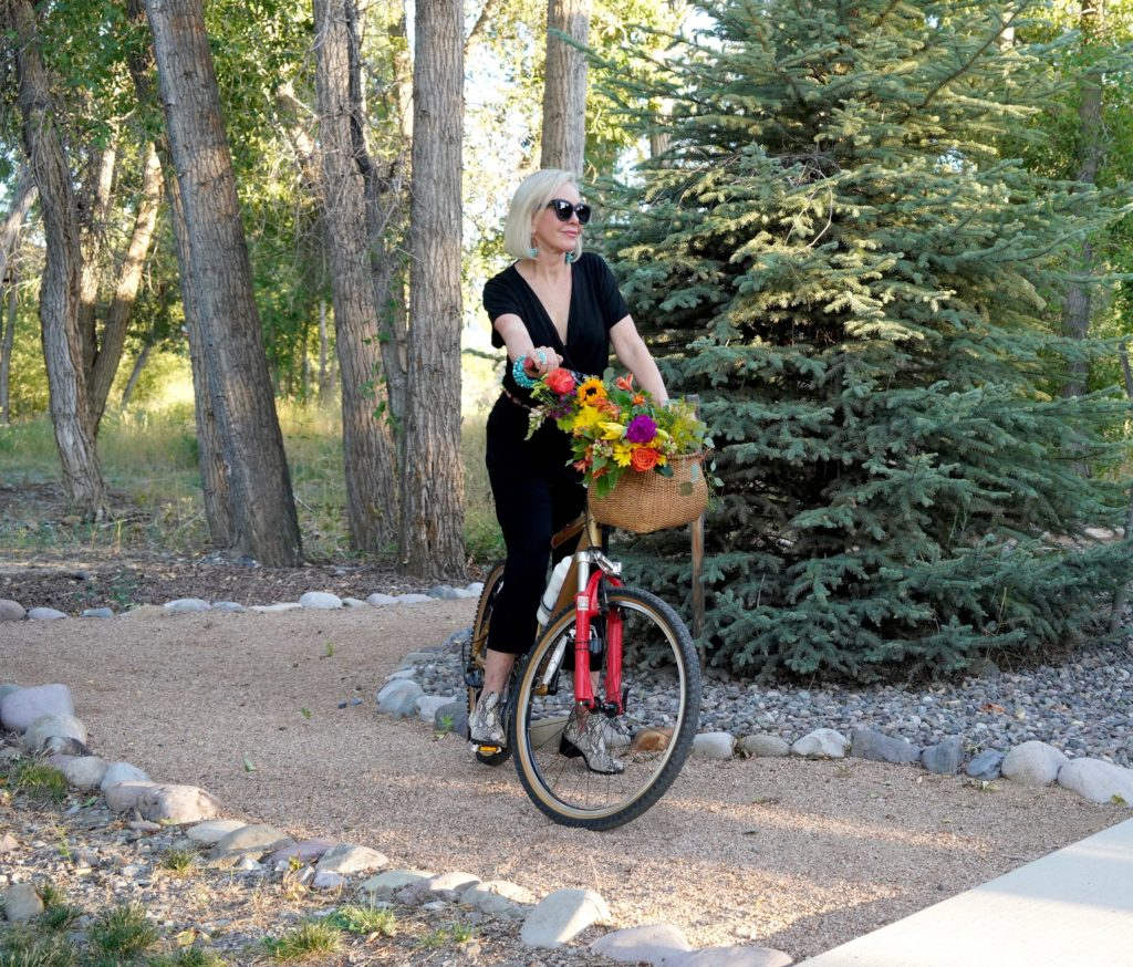 Sheree of the SheShe Show riding a bike with flowers in basket wearing a black jumpsuit