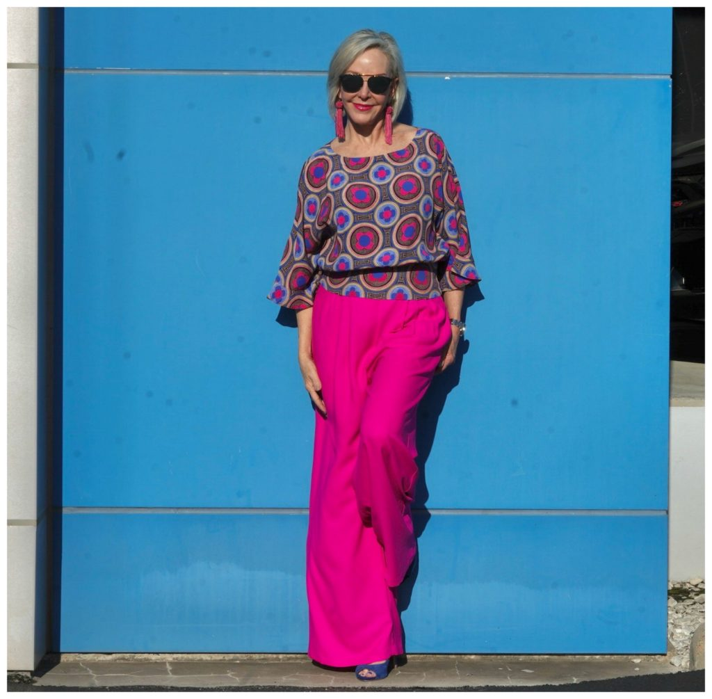 Sheree of the SheShe Show wearing hot pink wide leg pants and blue print top standing in front of blue wall