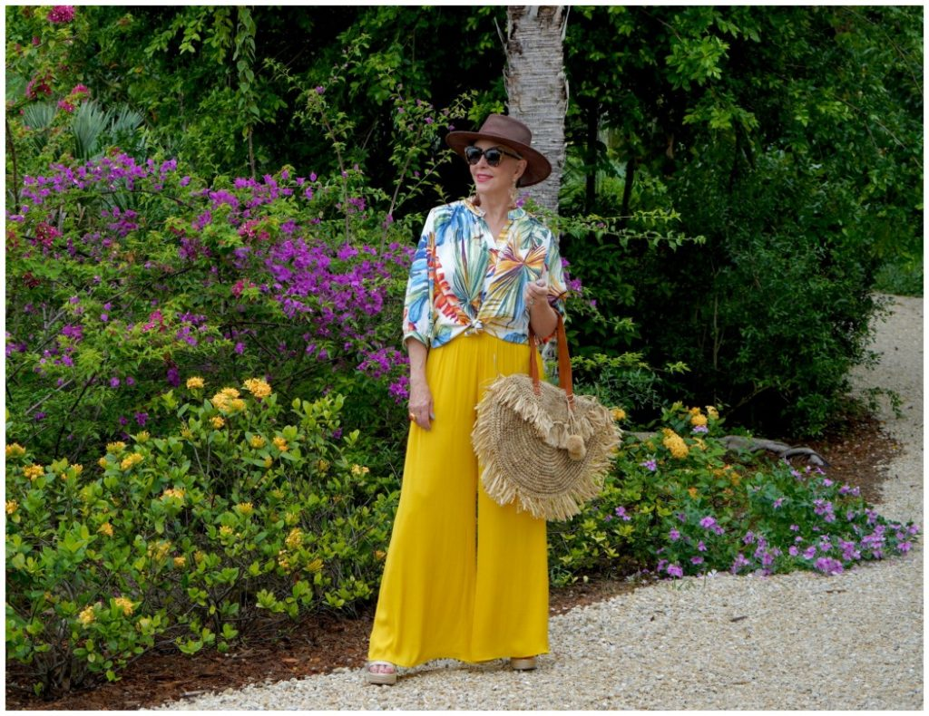 Sheree of the SheShe Show wearing yellow wide leg pants and tropical top with raffia tote bag