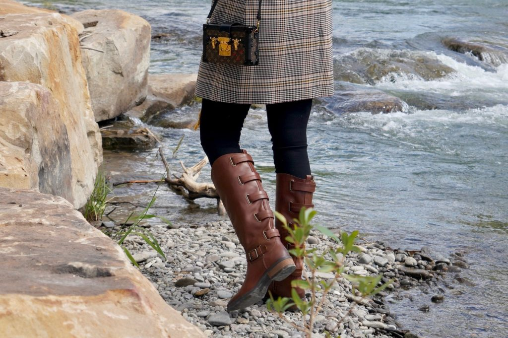 brown knee high boots worn with jeans and plaid blazer