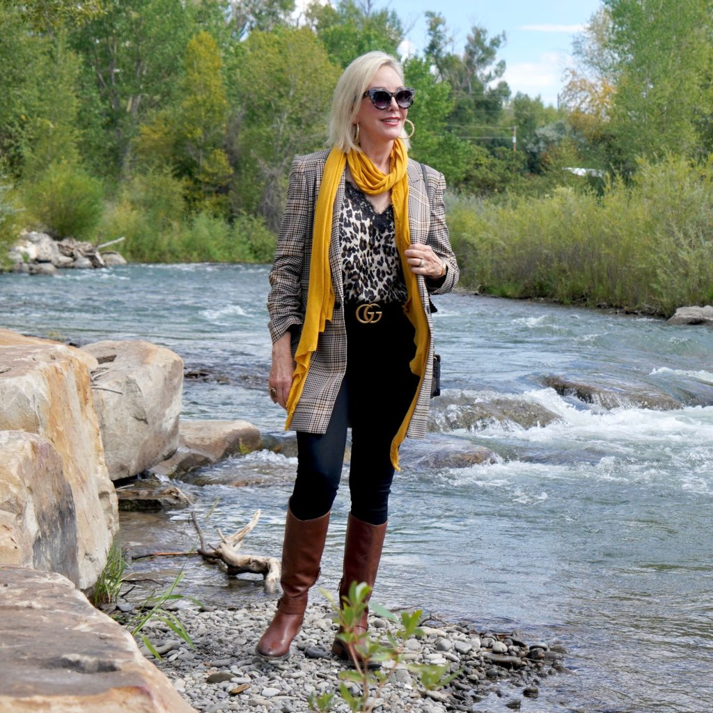 SheShe Show in plaid blazert over black jeans and brown boots walk ing the river