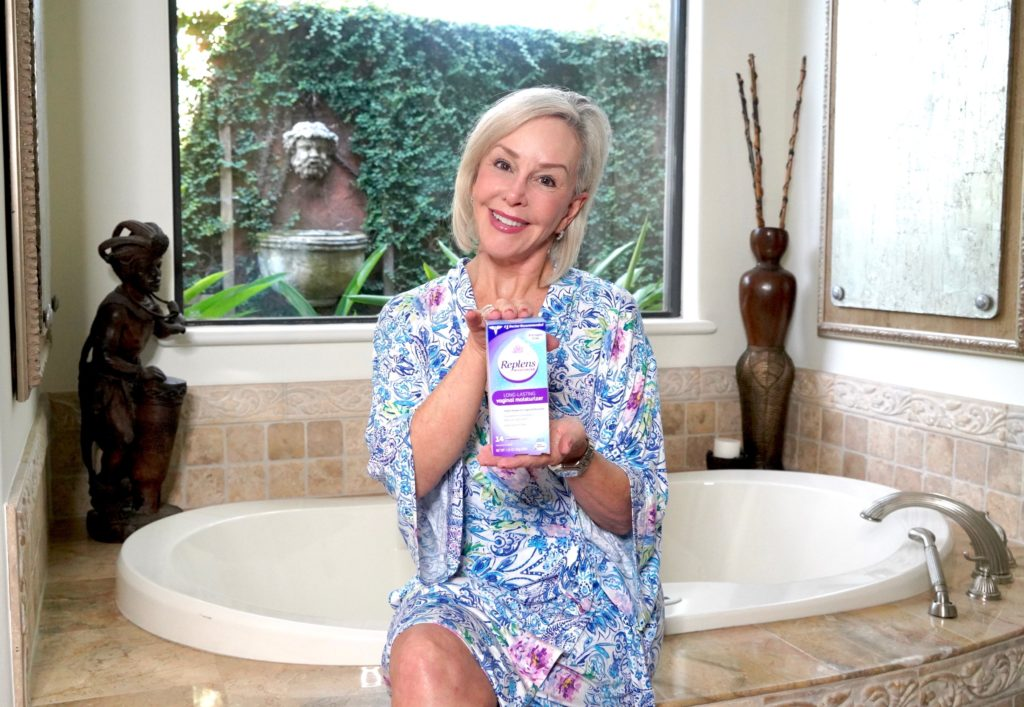 Sheree of the SheShe Show holding Replens box sitting on bathtub in a robe