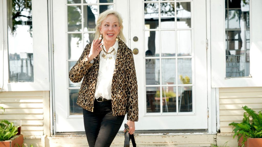 Sheree of the SheShe Show wearing Chico's leopard moto jacket over ivory ruffle blouse and black jeans with tan suede booties