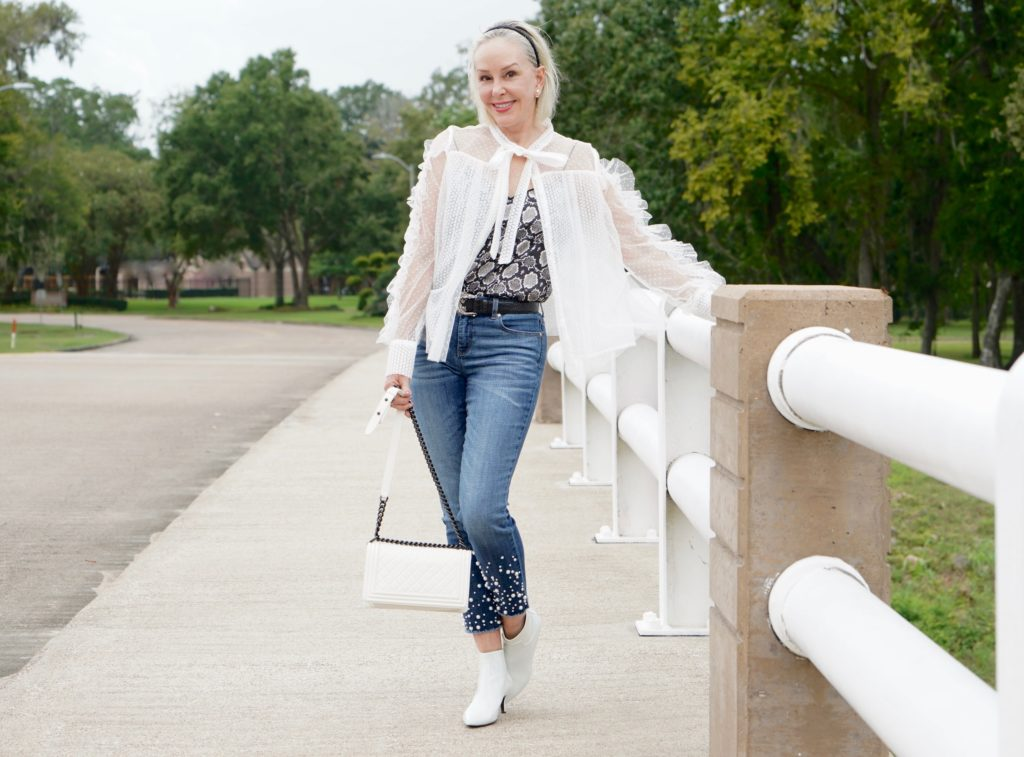 sheshe of the SheShe Show wearing white mesh and ruffle top over skinny crop jeans with pealrs