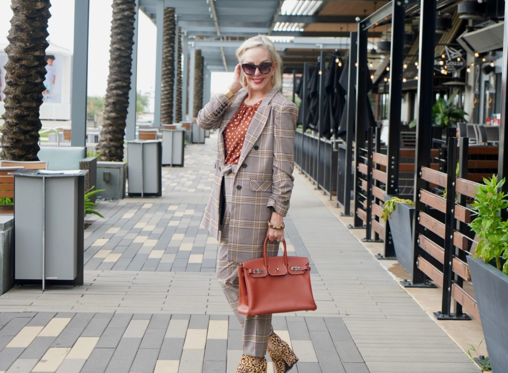 Sheree of the SheShe Show walking in front of outdoor mall wearing a plaid suit with rust with white polka dot tops and leopard booties