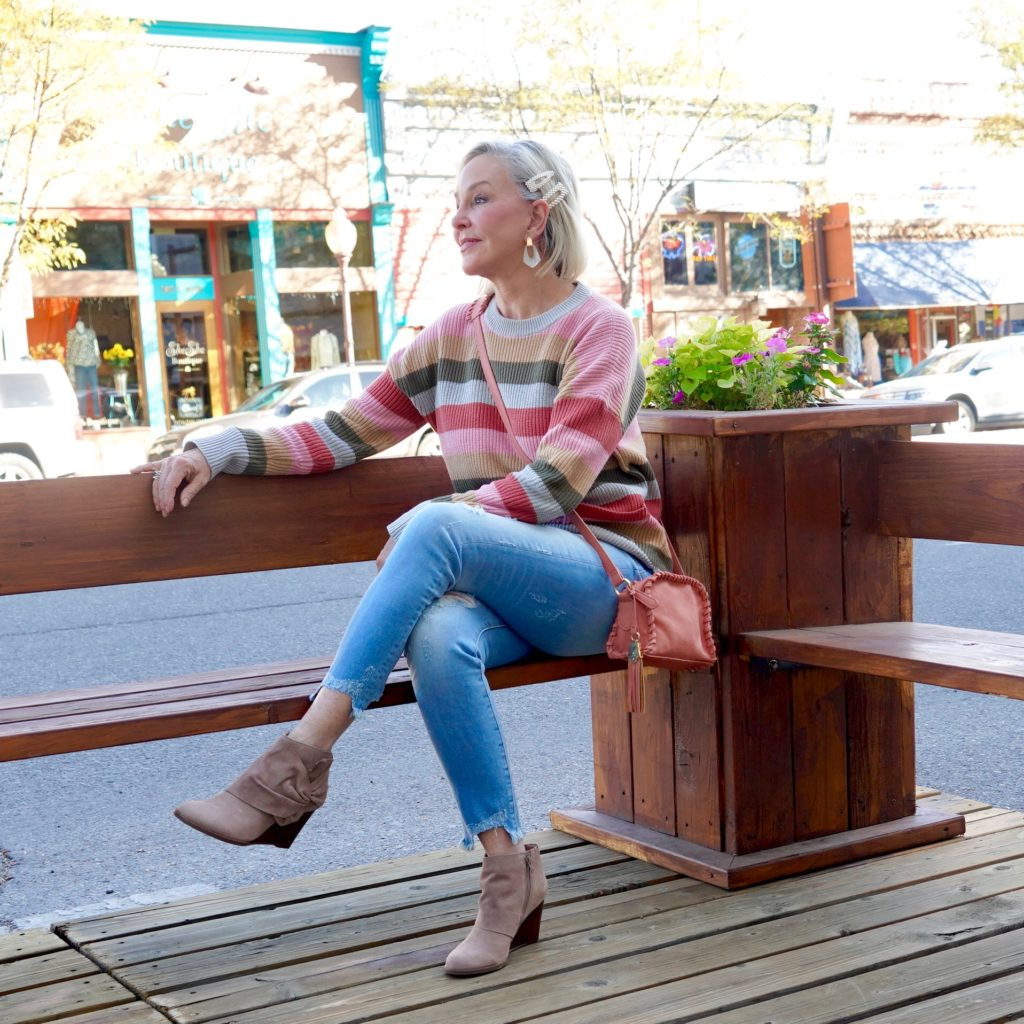 SheShe of the SheShe Show wearing stripe sweater jeans with booties