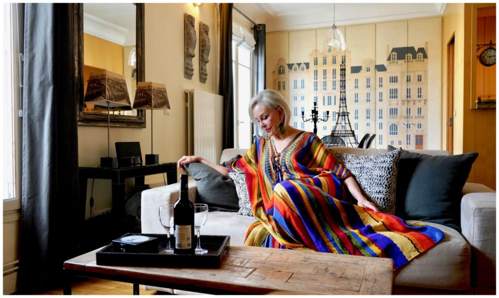 SheShe of the SheSheShow wearing a rainbow colored kimono lounging on a sofa at Paris Perfect apartment rentals