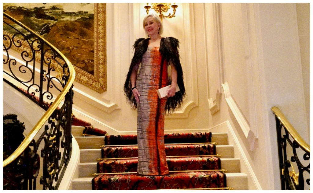 Sheree Frede of the SheShe Show standing on the grand staircase at the Ritz in Paris wearing a ball gown.