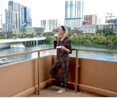 SheShe of the SheShe Show wearing leopard pj's on lake balcony in Austin