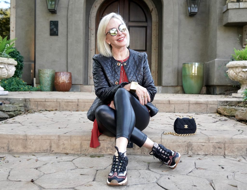 Sheree of the SheShe Show wearing a black moto jacket over faux leather leggings and black sneakers