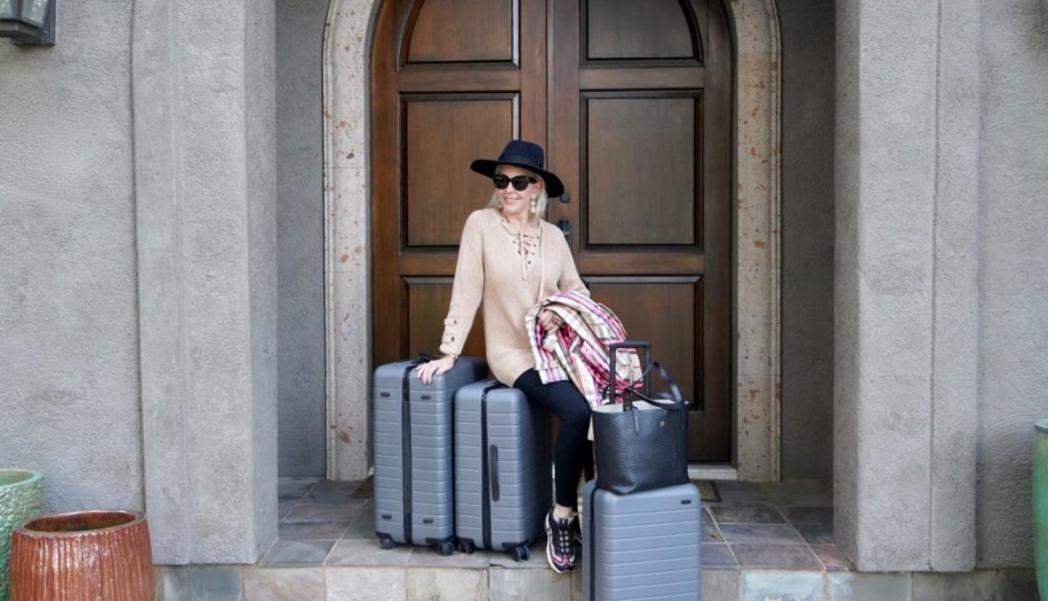 Sheree of the SheShe Show sitting with 3 large suitcases at her front door wearing black leggings, black hat and tan sweater.