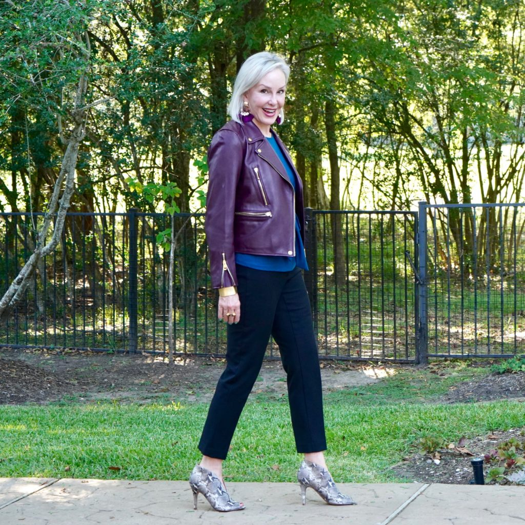 Sheree of the SheShe Show wearing a burgundy leather moto jacket over classic black pants and snakeskin booties