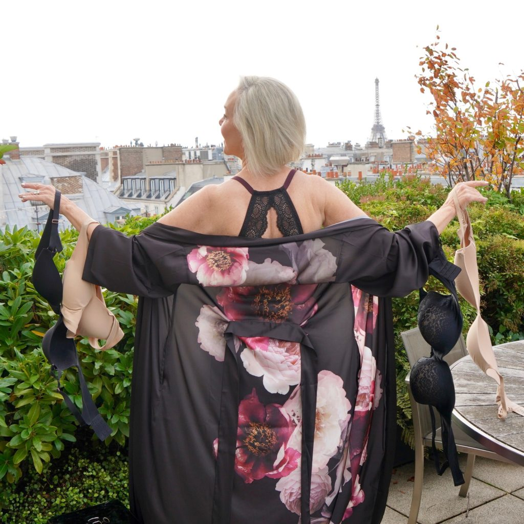 Sheree Frede of the SheShe Show wearing a long floral robe holding 4 bras