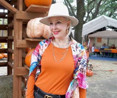Sheree Frede of the SheShe Show weqring orange top with colorful scarf as a wrap and off white hat