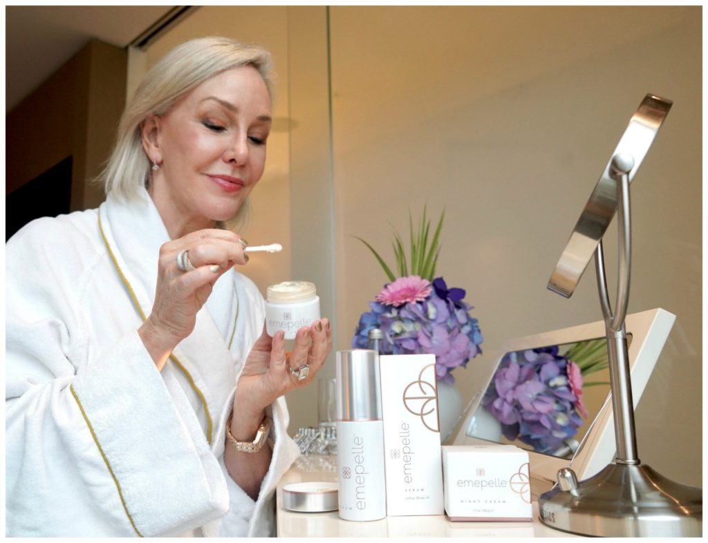 Sheree Frede of the SheShe Show sitting at vanity waring a white robe applying Emepelle cream