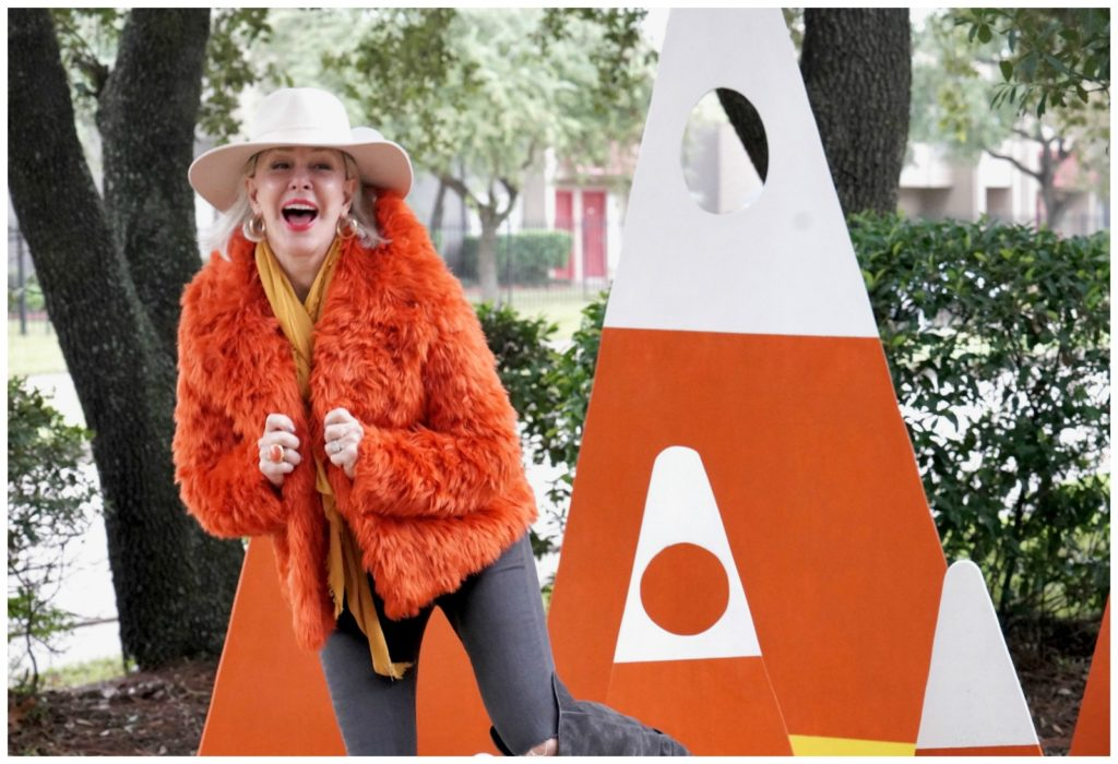 Sheree Frede of the SheShe Show standing in a candy corn patch wearing an orange faux fur jacket, jeans and white hat.