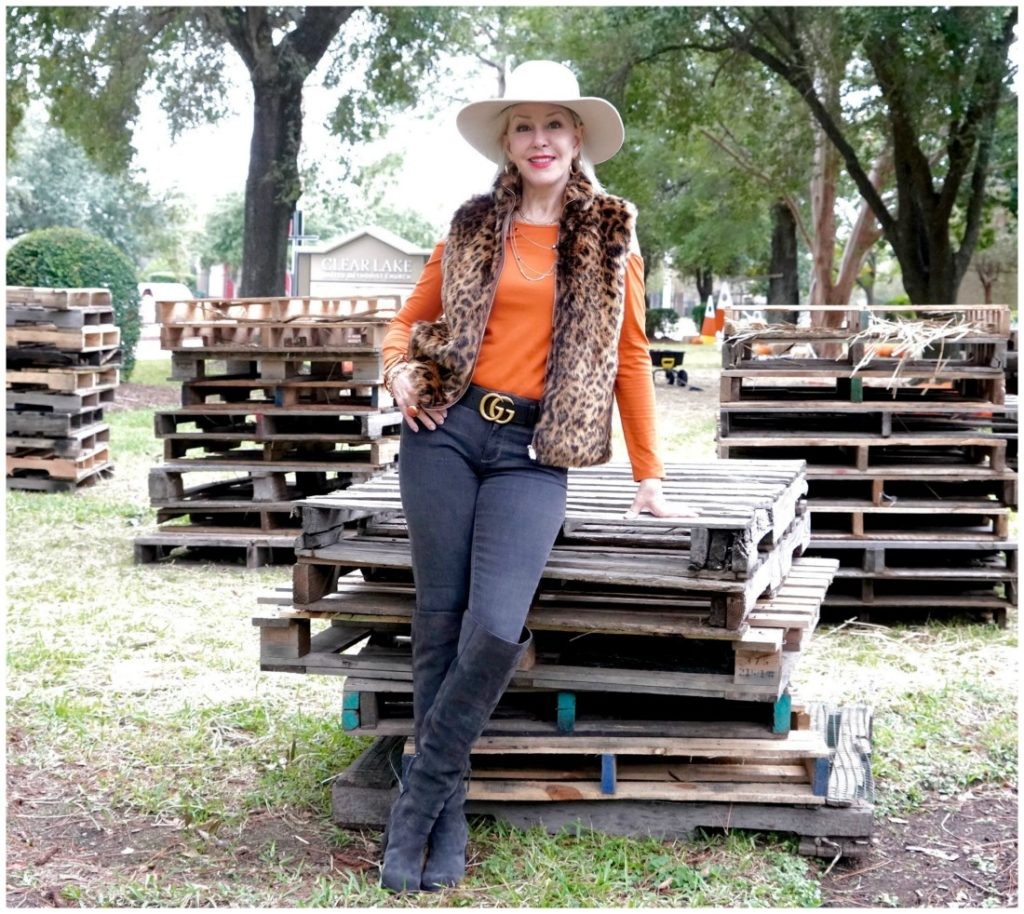 Sheree Frede of the SheSheShow wearing a leopard faux fur vest, jeans, boots, orange top and white hat