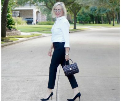 Sheree of the SheShe Show wearing basic black pants and white shirt with black pumps and Chanel bag