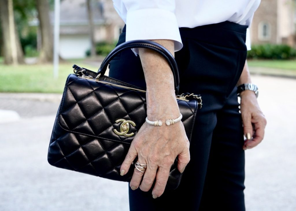 Up close photo of black Chanel handbag and David Yurman accessories.
