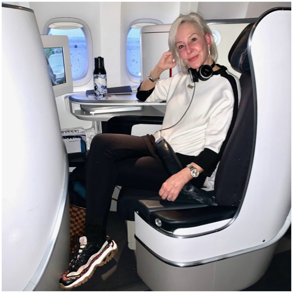 Sherere of the SheShe Show sitting in Air France Business First wearing white top with black leggings and sneakers