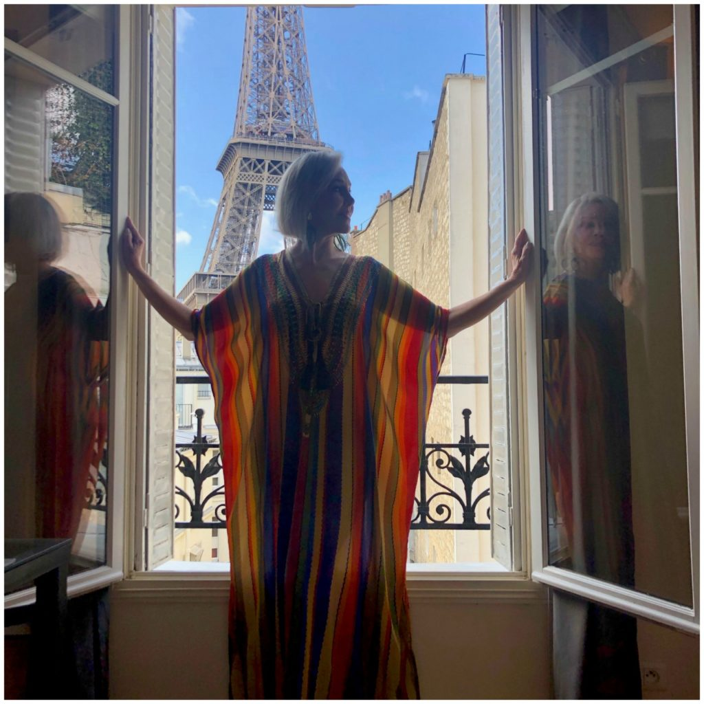 Sheree of the SheShe Show standing at window with Eiffel Tower in the background wearing a colorful stripe Kimono