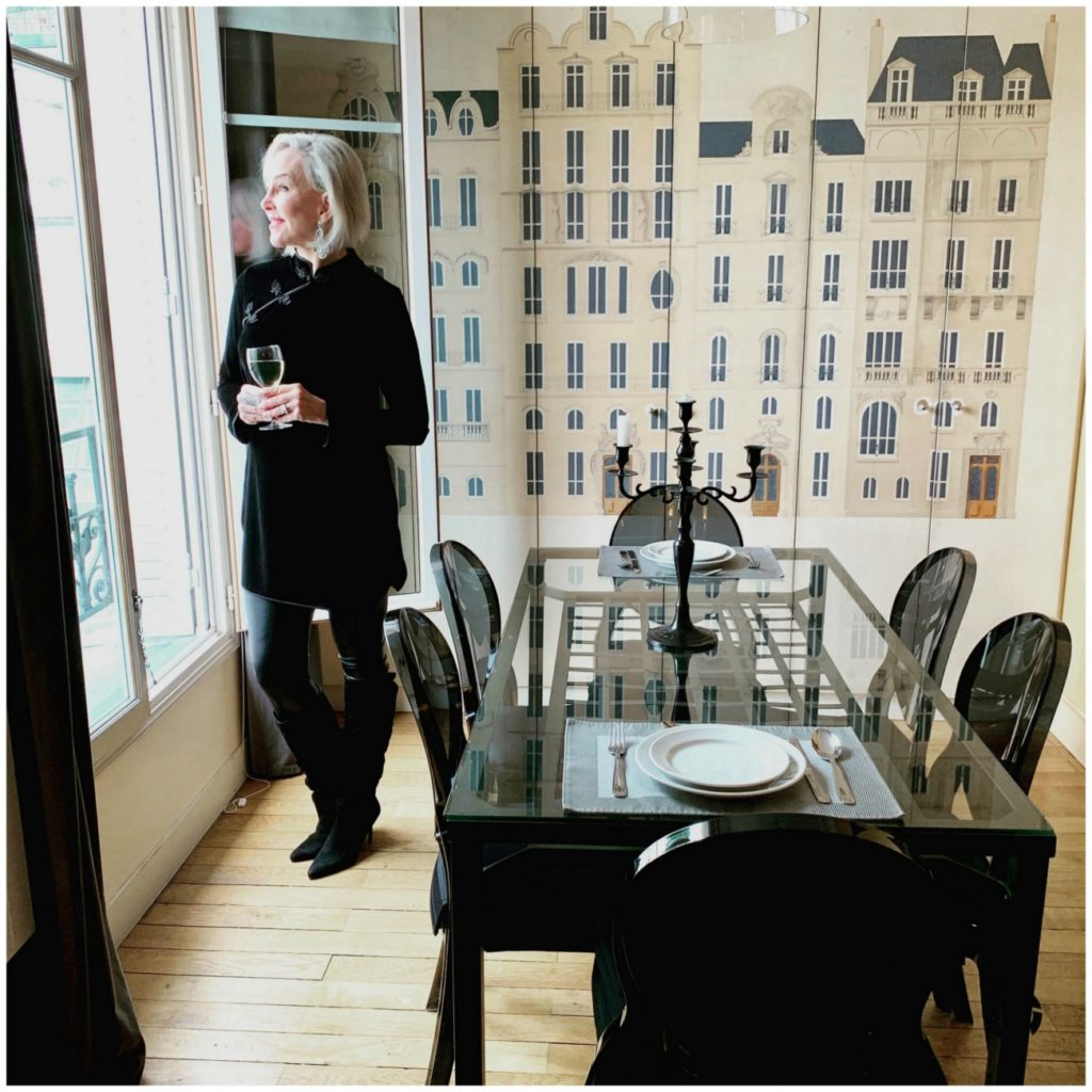 Sheree of the SheShe Show standing at window in dining room apartment in Paris wearing a black tunic and leggings