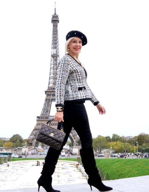 Sheree Frede of the SheShe Show walking and wearing black pants and black and whit knit jacket and beret.