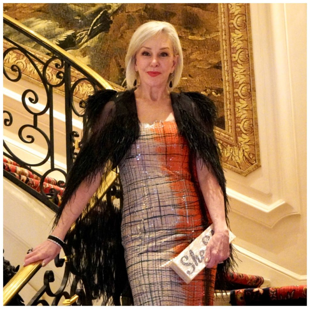 Sheree of the SheShe Show standing on grand staircase wearing an orange sequin gown and black mesh caplet