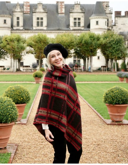 Sheree of the SheShe Show standing in front of big castle wearing a knit poncho and black beret