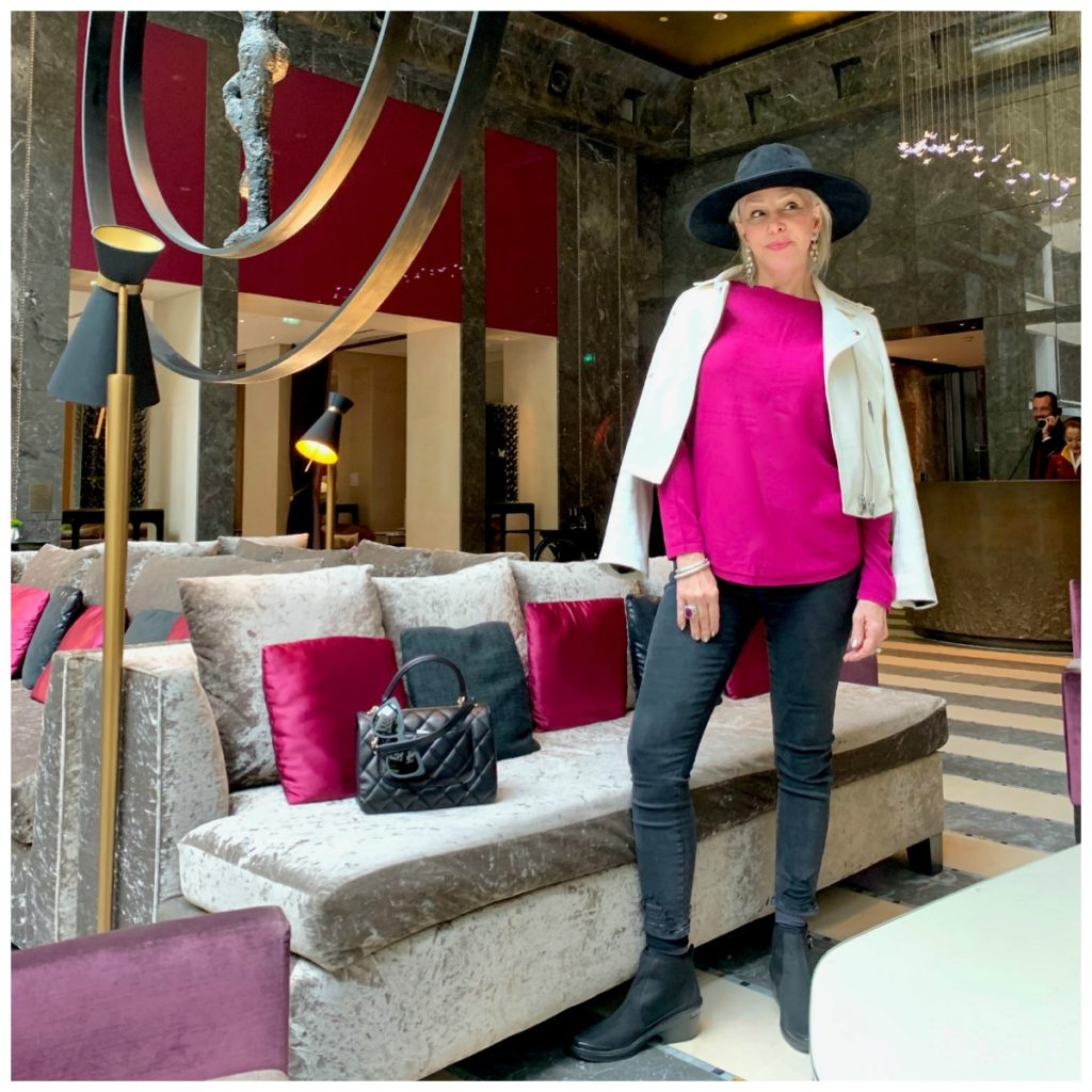 Sheree of te SheSheShow wearing fucshia top, white leather moto jacket, gray jeans and black hat