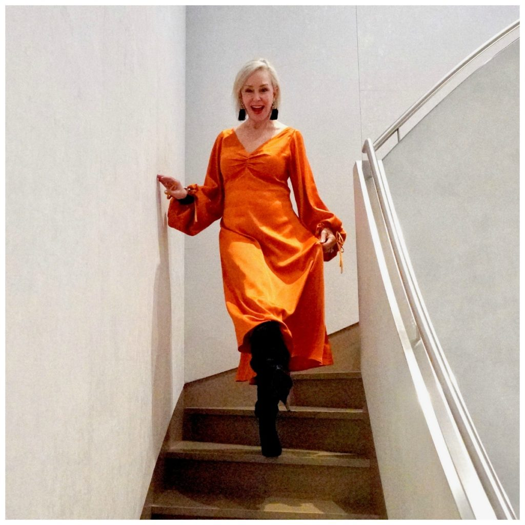 Sheree of sheshe show wearing an orange satin midi dress on stairs