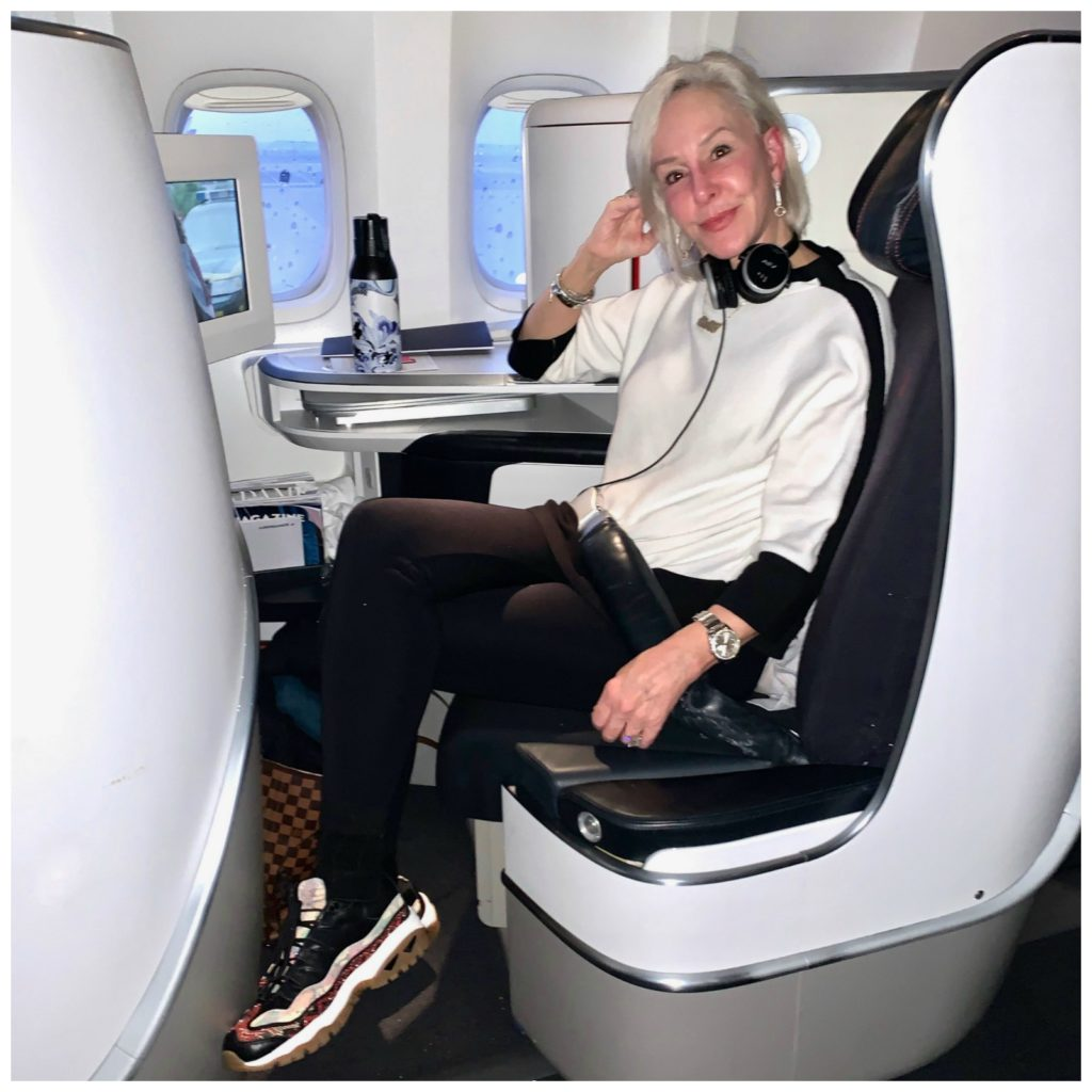 Sheree sitting in chair on plane to Paris wearing all chicos outfit and skechers sneakers